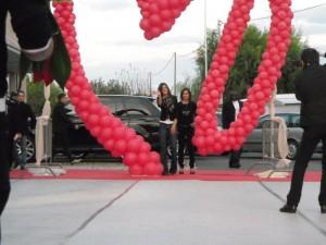 allestimento scenografico con struttura di palloncini rossi sotto cui sfila elisabetta canalis