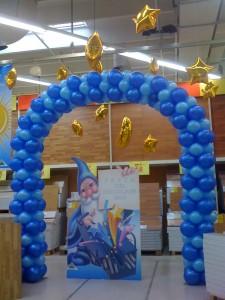 Allestimenti con palloncini e animazioni, arco di palloncini blu e azzurro e stelle dorate appese al soffitto.