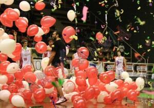 cascata di palloncini bianchi e rossi con kabuki colorati in un campo di basket