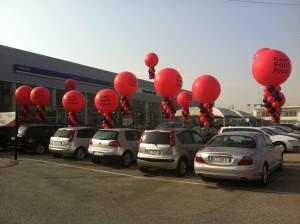 Mongolfiere promozionali rosse appese alle auto di una concessionaria