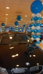 Allestimenti con palloncini stampati, colonne di palloncini blu e bianco accanto alla nuova bmw