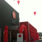 colonne di palloncini rossi, arco di palloncini rossi e palloni giganti rossi gonfiati ad elio sospesi sul tetto