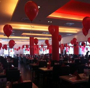 palloncini rossi gonfiati ad elio legati a sedie e tavoli del ristorante