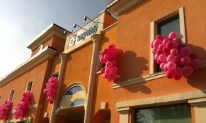 anniversario aziendale Outlet Palmanova, dalle finestre fuoriescono cascate di palloncini rosa