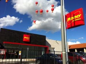 palloni giganti stampati per inaugurazioni: decine di palloni giganti rossi sospesi sul tetto di un supermercato