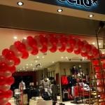 arco gigante di palloncini bianchi e rossi all'esterno di un negozio