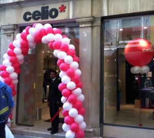 arco di palloncini bianchi e rossi posizionato all'ingresso di un negozio celio