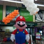 Gonfiabile gigante di super mario con rullo e cacciavite di palloncini sullo sfondo