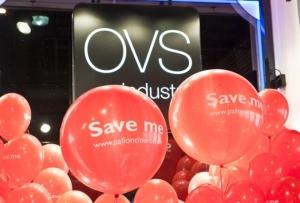 palloni giganti rossi con stampa bianca, sfondo nero con logo OVS
