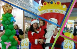 babbo natale e natalina tengono in braccio un bimbo per la foto