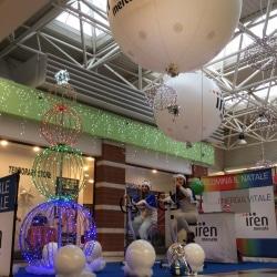 palloni giganti bianchi gonfiati ad elio sospesi su un allestimento luminoso