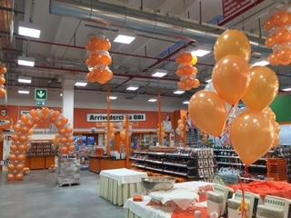 Allestimento con palloncini, arco argento e arancio, ciuffi di palloncini arancioni ad elio e lampadari di palloncini appesi al soffitto
