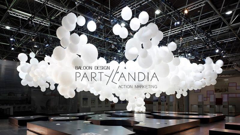 scenografie per stand fieristici: una coreografia di palloni bianchi con marchio partylandia in primo piano