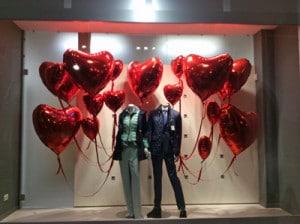 allestimento vetrine creativo per san valentino: due manichini tengono in mano ciuffi di palloni a forma di cuore