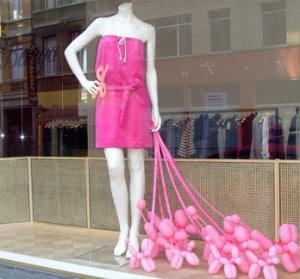 allestimento vetrine creativo: manichino vestito di fucsia tiene in mano dei palloncini rosa