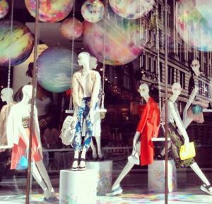 vetrina con manichini donne e palloni giganti sospesi