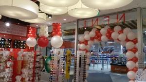 allestimento vetrine creativo: arco di palloncini bianchi e rossi e palloni giganti capovolti scendono dal soffitto
