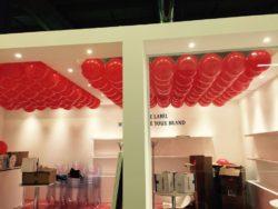 Allestimento stand fiera con palloncini rossi sul soffitto