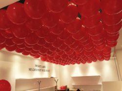 Allestimento stand fiera con palloncini rossi e tondi sul soffitto