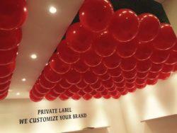 Allestimento stand fiera con palloncini rossi appesi uno ad uno sul soffitto